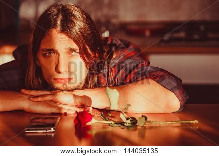 Disappointment and depression. Unrequited love concept. Young worried disappointed man with single red rose and smartphone mobile phone waiting for his girlfriend.