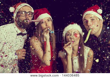 Two beautiful young couples in love blowing party whistles at a New Year's Eve party