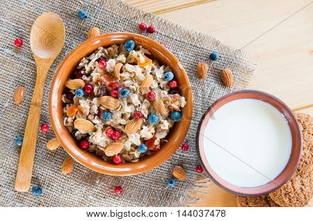 Serving Muesli Scattering Of Wild Berries, Nuts, Milk On Table