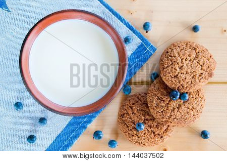 Milk In Clay Mug With Oatmeal Cookies On Wooden Table.