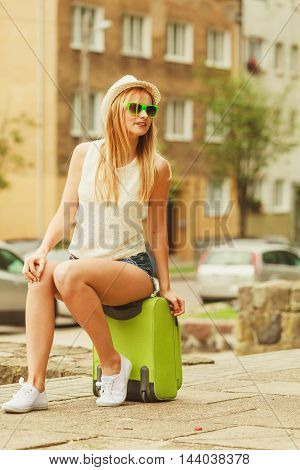 Woman Traveler Sits On Suitcase Waiting For Car.