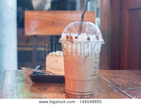 Take-home ice coffee cup on wooden table, stock photo