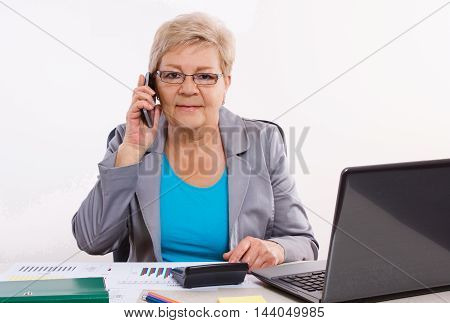 Elderly Business Woman Talking On Mobile Phone And Working At Her Desk In Office, Business Concept