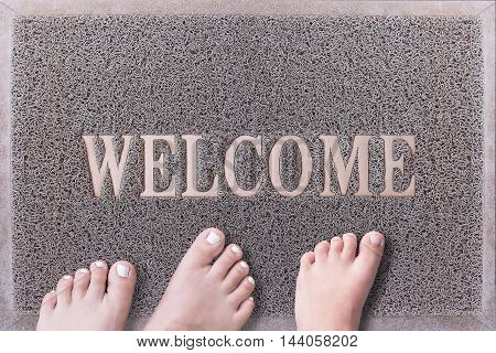 Welcome Door Mat With Three Feet. Friendly Grey Door Mat Closeup with Bare Feet Standing. Welcome Carpet. Three Feet on Foot Scraper.