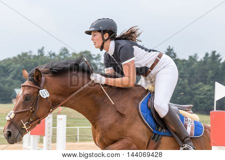 SVEBOHOV CZECH REPUBLIC - AUG 20: Closeup side view of horsewoman jumping a brown horse at