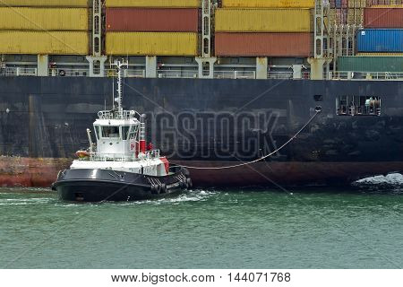 a tug boat moving a large container ship into place along side a harbor quay