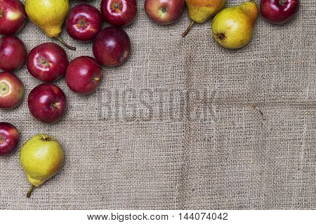 Ripe apples and pears on a jute cloth rustic background