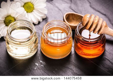 Honey In Jar With Honey Dipper On Black Stone Background