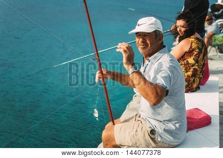 Pefkohori Greece - May 26 2015: Man wearing a cap shows his catch while fishing in the Aegean sea