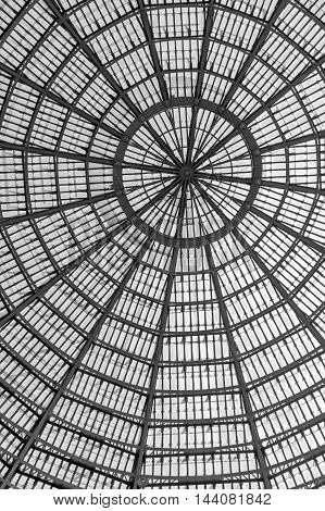 Multiple glass windows as part of domed ceiling. Black and white vertical format with metallic and glass dome structure detail under blue sky.