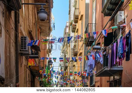 Naples (Napoli) Italy - June 11: Streets of Naples June 11 2016 in Naples Italy. Many international small flags hanging from ropes along streets.