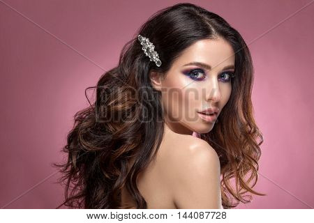 Beauty woman face with beautiful make-up color . Dark hair raised hair jewelry on his neck clean skin beautiful face . Portrait shot in studio on a pink background .
