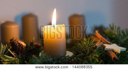 burning candle on homemade Advent wreath - closeup