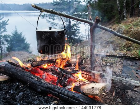 Cooking on the fire for a camping trip. Pot over a fire outdoors.