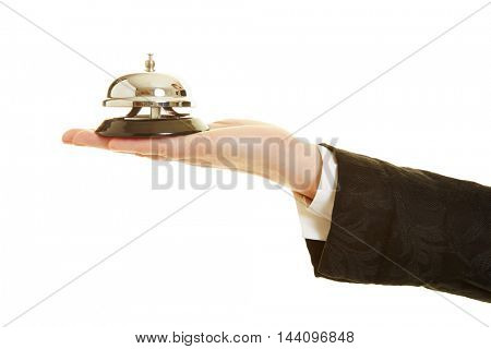 Hand of a female concierge holding a hotel bell