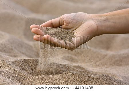 sand running through fingers in the beach