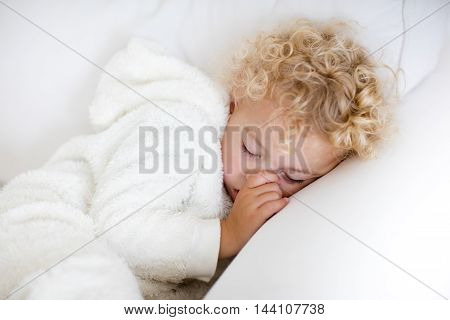 Cute blond curly little boy sleeping on white couch. Tired toddler taking a nap wearing warm white pajamas sucking his thumb.