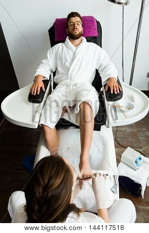 Portrait of young man doing pedicure in salon. Beauty concept.