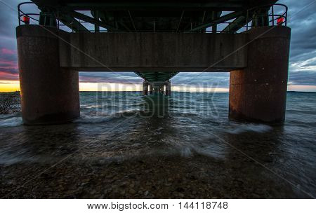 Under The Mackinaw Bridge in Michigan. Sunset horizon from the underneath the mighty Mackinac Bridge in Michigan. The Mackinaw Bridge is one of the longest suspension bridges in the world and connects the Upper and Lower Peninsulas of Michigan.