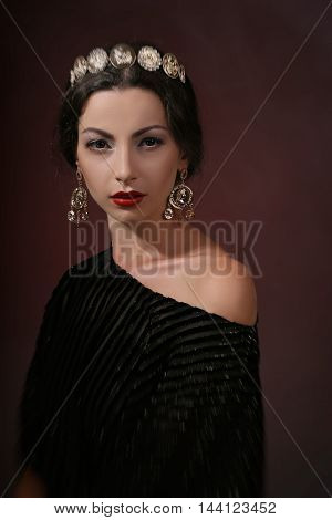 beautiful young brunette in a luxurious gold jewelery