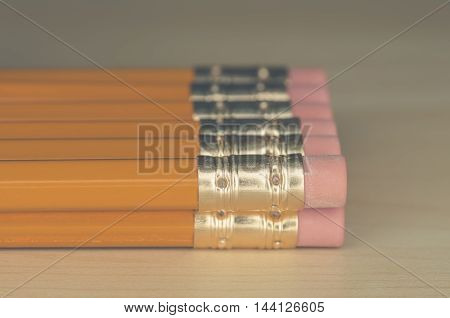 Many pencils stacked on each other on a desk