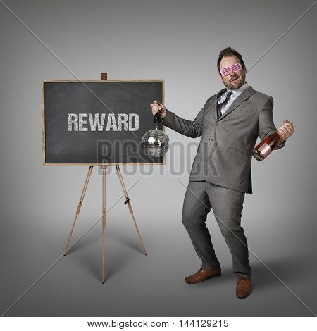 Reward text on blackboard with drunk businessman
