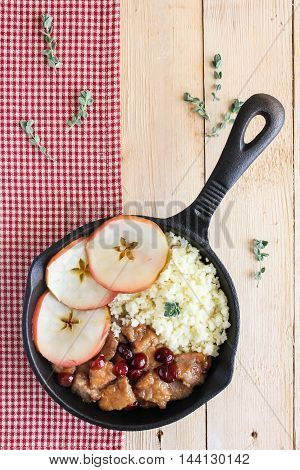 Pork stew with dried cranberry served with couscous in a pan, selective focus