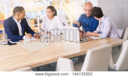Business meeting taking place with diverse group of business people in a modern office with several electronic devices at their aid, including the tablet being held by one of the executives.