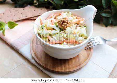 Fresh salad with white cabbage, carrot, apples and pears with walnuts and yogurt dressing in a bowl, selective focus  Fresh salad with white cabbage, carrot, apples and pears with walnuts and yogurt dressing in a bowl, selective focus