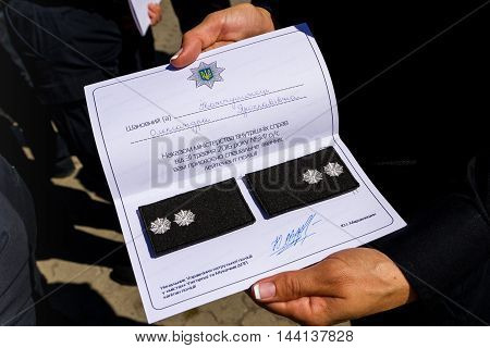 Uzhgorod Ukraine - August 25. 2016: Police woman shows the new epaulets of lieutenant during the ceremony of awarding titles to inspectors of police officers.