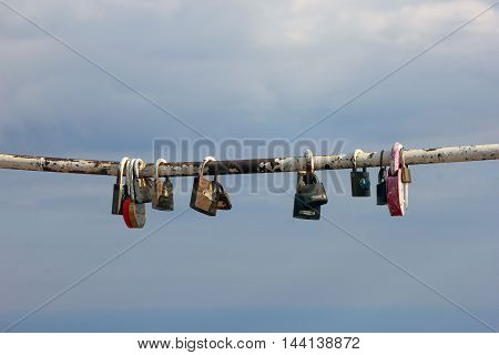 multiple padlocks hung on the metal pipe to the memory on sky background