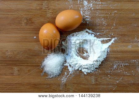 Sugar, flour and eggs with wooden background. All the ingredients normally used for baking cake and muffins