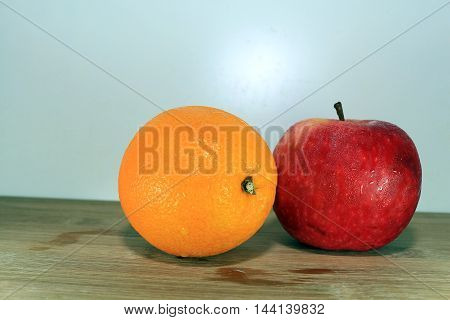 A Ripe Red Apple with orange fruit on a wooden background