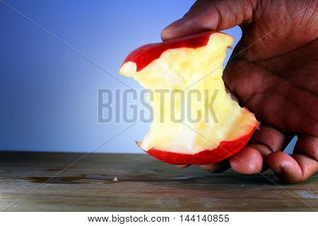 a half bitten apple with wooden background and isolated