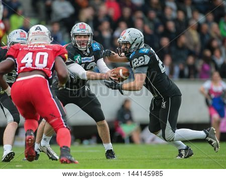 INNSBRUCK, AUSTRIA - MAY 2, 2015: QB Sean Shelton (#12 Raiders) hands the ball to RB Fabien-Andre Gaertner (#22 Raiders) in a game of the Big SIx Football League.