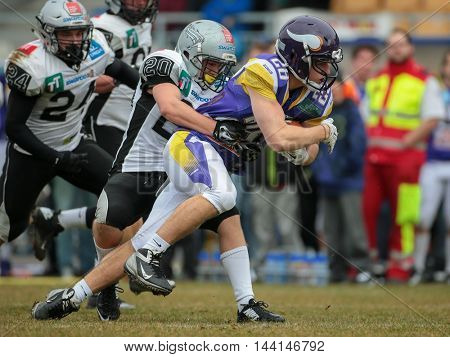 VIENNA, AUSTRIA - MARCH 22, 2015: DB Patrick Pilger (#20 Raiders) tackles RB Alexander Hertel (#28 Vikings) in a game of the Austrian Football League.