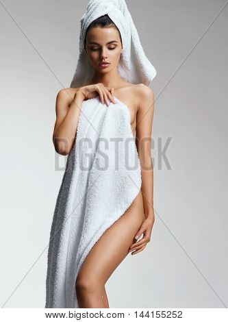 Sexy woman in towel after bath. Beautiful healthy naked woman on gray background. Beauty & Skin care concept.