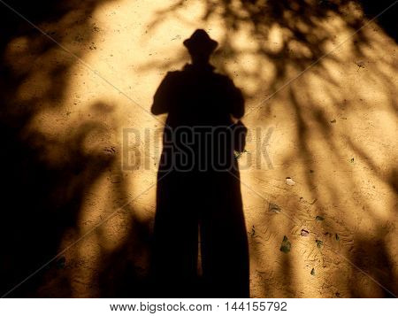 Eerie picture of a shadow man on sandy ground