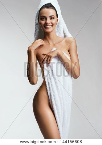 Happy smiling woman after spa treatments. Photo of Beautiful slim woman in towel covering her breast. Wellness and Spa concept