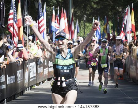 NEW YORK JUL 24 2016: Athlete crosses the finish line of the NYC Triathlon Race in Central Park. The run is 10 kilometers and the race is the only International Distance triathlon in the city.