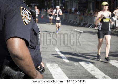 NEW YORK -?? JUL 24 2016: Members of the NYPD patrol the route on West 72nd St for athletes running the 10k part of the NYC Triathlon Race. The race is the only International Distance triathlon in NYC.