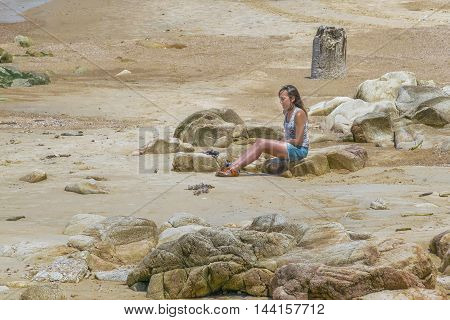 MONTEVIDEO, URUGUAY, - DECEMBER - 2015 - Young woman sitting on rocks at beach in Montevideo Uruguay