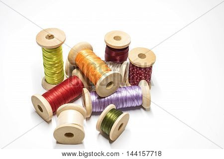 Wooden spools with satin ribbons on white