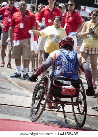 NEW YORK JUL 24 2016: ParaTriathlete from CAF, Challenged Athletes Foundation, in a modified wheelchair crosses the finish line in Central Park in the NYC Triathlon Race.