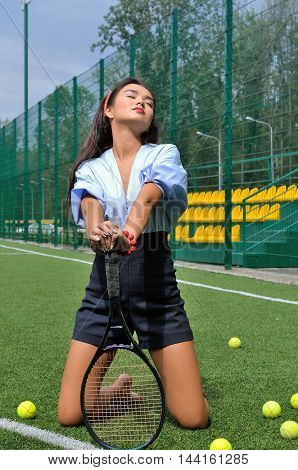 Woman Kneeling On The Tennis Court Relying On The Racket.