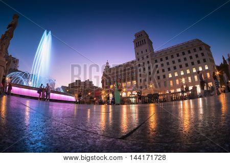 Night view of Barcelona's Plaza Catalunya with fountain