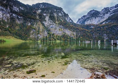 Berchtesgaden in Germany on the border with Austria. Famous lake Konigssee. Walking tourist boat approaches the pier