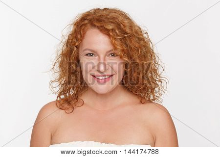 Emotions concept. Portrait of smiling and positive mature or middle aged woman looking at camera isolted onwhite background in studio.