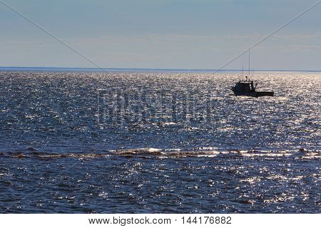 Lobster boat silhouetted against the sparkling sea.