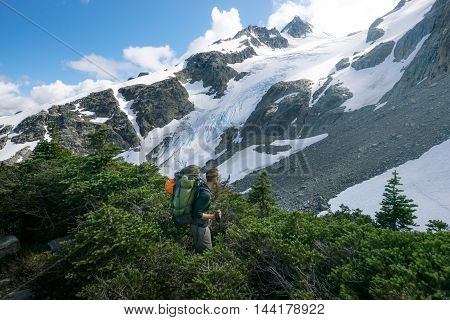 A mountain climber pauses to find his route